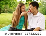 Long-haired girl feeds the guy a big candy - stock photo