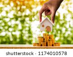 investor hand hold a home model ... | Shutterstock . vector #1174010578