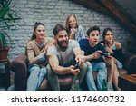 Small photo of Group of friends are gathered at their friends apartment to enjoy and play some video games together.