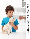 Boy at the veterinary doctor with his little doggy receiving medication - stock photo