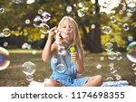 happy little girl in autumn... | Shutterstock . vector #1174698355