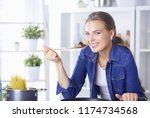 young woman cooking healthy... | Shutterstock . vector #1174734568