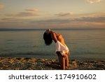 woman stands on knees on beach... | Shutterstock . vector #1174910602