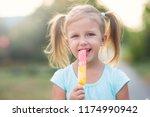 little beautiful girl eating... | Shutterstock . vector #1174990942
