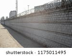 brick fence with barbed wire... | Shutterstock . vector #1175011495