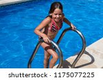 small girl in the swimming pool. | Shutterstock . vector #1175077225