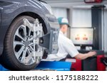 Small photo of Closed up of an auto wheel : computer wheel alignment. Balancing tire wheel machine. Tyre assembling. Tyre balancing of modern car in workshop.