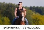 Small photo of Strong man bodybuilder in a black t-shirt, denim pants, sunglasses riding a horse