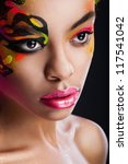 portrait of the dark-skinned girl with unusual make-up on dark background - stock photo