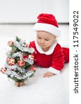 My first christmas - baby girl in santa outfit with small decorated tree - stock photo