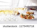 Small photo of solemn happy new year banquet. Lot of glasses champagne or wine on the table in restaurant. buffet table with lots of delicious snacks. canapes, bruschetta, and little desserts on wooden plate board