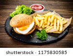 tasty burger with chips served... | Shutterstock . vector #1175830585