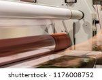 Big printing machine and laminator, armed with red rolls and transparent film.