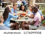 friends sitting at table in pub ... | Shutterstock . vector #1176099508