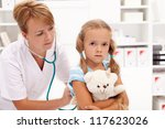 Little girl at the doctor - health professional checking her with stethoscope - stock photo