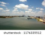 Small photo of Cargo ship movement to the outlet via the shipping channel of the port of Brownsville, USA. A view of the coastline, berths and old of rusty ships, warships decommissioned for scrap.July 2018.