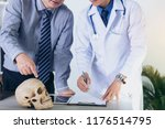 doctor is holding a human skull ... | Shutterstock . vector #1176514795