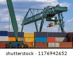 green crane loads over stacked... | Shutterstock . vector #1176942652