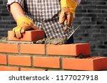worker builds a brick wall | Shutterstock . vector #1177027918