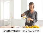 young woman pouring fresh... | Shutterstock . vector #1177679245