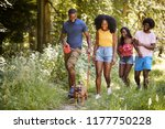Stock photo two black couples walking with a dog in a forest 1177750228