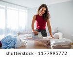 smiling young woman ironing... | Shutterstock . vector #1177995772