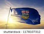 Alberta flag textile cloth fabric waving on the top sunrise mist fog