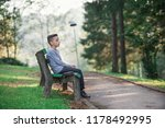 boy sits on a bench in the park | Shutterstock . vector #1178492995