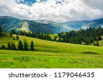 Small photo of beautiful green valley with coniferous forest. wonderful landscape in mountains. huge cloud almost cover the sky. lovely early autumn scene