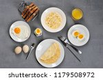 Small photo of Different dishes from chicken eggs. Omelette, soft-boiled, hard-boiled, fried, scrambled eggs. In the frame, toasts and a glass of juice. Close-up. View from above. Gray background.