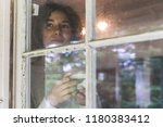 woman looking out through an... | Shutterstock . vector #1180383412