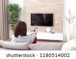 young woman watching tv in the... | Shutterstock . vector #1180514002