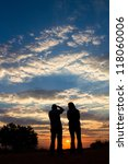 A couple taking photographs of a spectacular sunset in the Kalahari desert - stock photo