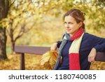 young beautiful woman in autumn ... | Shutterstock . vector #1180740085