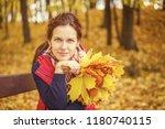 young beautiful woman in autumn ... | Shutterstock . vector #1180740115