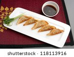 Fried thai gyoza dumpling appetizers with soy dipping sauce. - stock photo