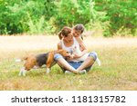 Stock photo young mother and her daughter playing with their cat and dog 1181315782