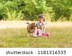 Stock photo portrait of girl sitting on a grassy ground together with her pets 1181316535