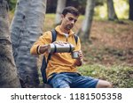 young man resting on wooden log ... | Shutterstock . vector #1181505358