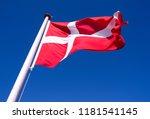 "Small photo of Flags / Laesoe / Denmark: The Danish national flag ""Dannebrog"" is fluttering in the gusty coastal wind on Laesoe island"