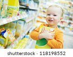 One little child choosing produces during food shopping in grocery store supermarket - stock photo