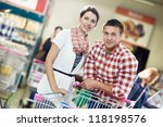 Young Family couple with trolley cart in meat grocery supermarket during weekly food shopping - stock photo