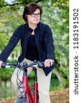 woman riding a bicycle in... | Shutterstock . vector #1183191502