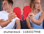 Young Couple Holding Halves Of...