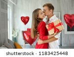 Stock photo young couple with gift box hugging at home 1183425448