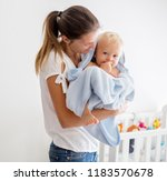 mother holding little baby... | Shutterstock . vector #1183570678