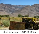 Iconic Owens Valley, California, late summer landscape, with rolling hills, colorful field and clear blue sky, accented by old rusted mining equipment in foreground.