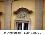 Small photo of Ancient bas-reliefs on the Windows and walls of historical buildings. Architectural design elements from the past. Warsawa. Ax, poleaxe on the crown of the window