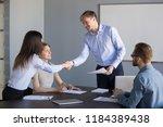 smiling boss handshaking female ... | Shutterstock . vector #1184389438