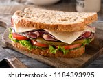 Small photo of A delicious ham and cheese sandwich with lettuce, tomato and dill pickle on a rustic wood table.
